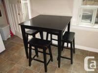 Tall black wooden table with 4 matching stools.  Table