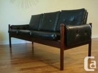 Vintage Teak and black vinyl three seat sofa.