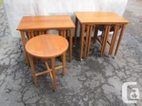 Two Teak end tables with seven smaller nest of tables