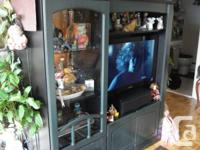 Large dark green / black tv unit. television in photos