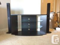 A modern black TV stand with two glass shelves in great