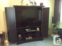 Solid closing TV wall unit with closing side shelves.