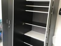 Two black shelf cabinets with doors , key lock and