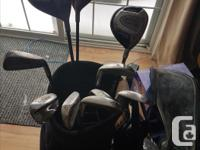 two sets of right hand golf clubs with bags and rain