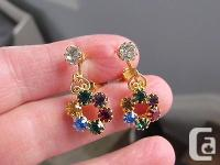 This is a pair of goldtone and multi colored rhinestone