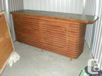 This vintage (1960s) solid wood bar with decorative