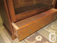 Solid walnut cabinet with lower drawer. Glass paneled