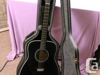 Yamaha acoustic guitar. Black guitar with hard case.