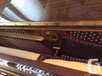A beautiful Young Chang walnut piano. 47 inches high.